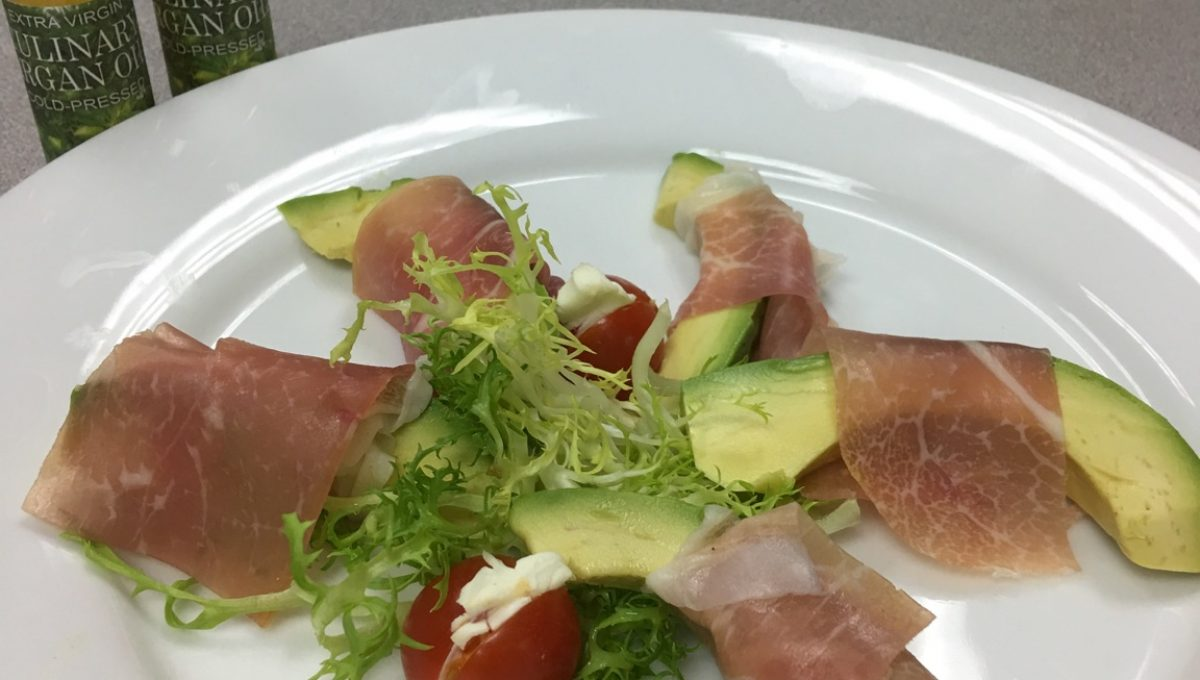 AVOCADO WRAPPED IN PROSCIUTTO HAM WITH A SIDE OF FRISEE SALAD FEATURING ARGAN OIL